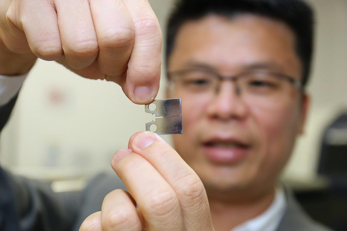 Professor Huang Mingxin shows a sample of the new super steel