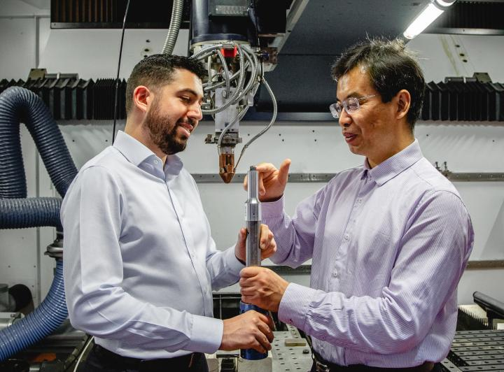 Researchers Carmelo Todaro and Ma Qian inspect a 3D-printed titanium alloy cube