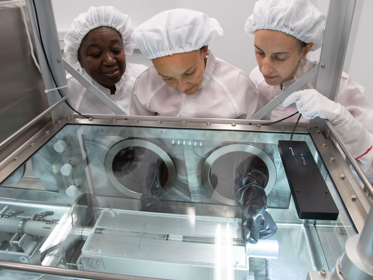 Scientists Andrea Mosie, Charis Krysher and Juliane Gross open the first lunar sample in more than 40 years at NASA's Johnson Space Center in Houston
