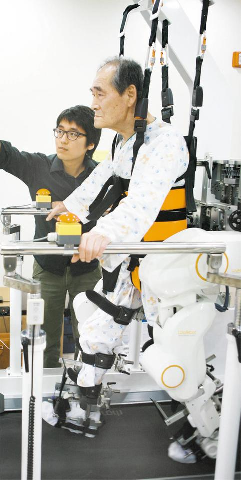 A physical therapist works with a patient walking with the Walkbot gait training system (Photo: Daejonilbo.com)