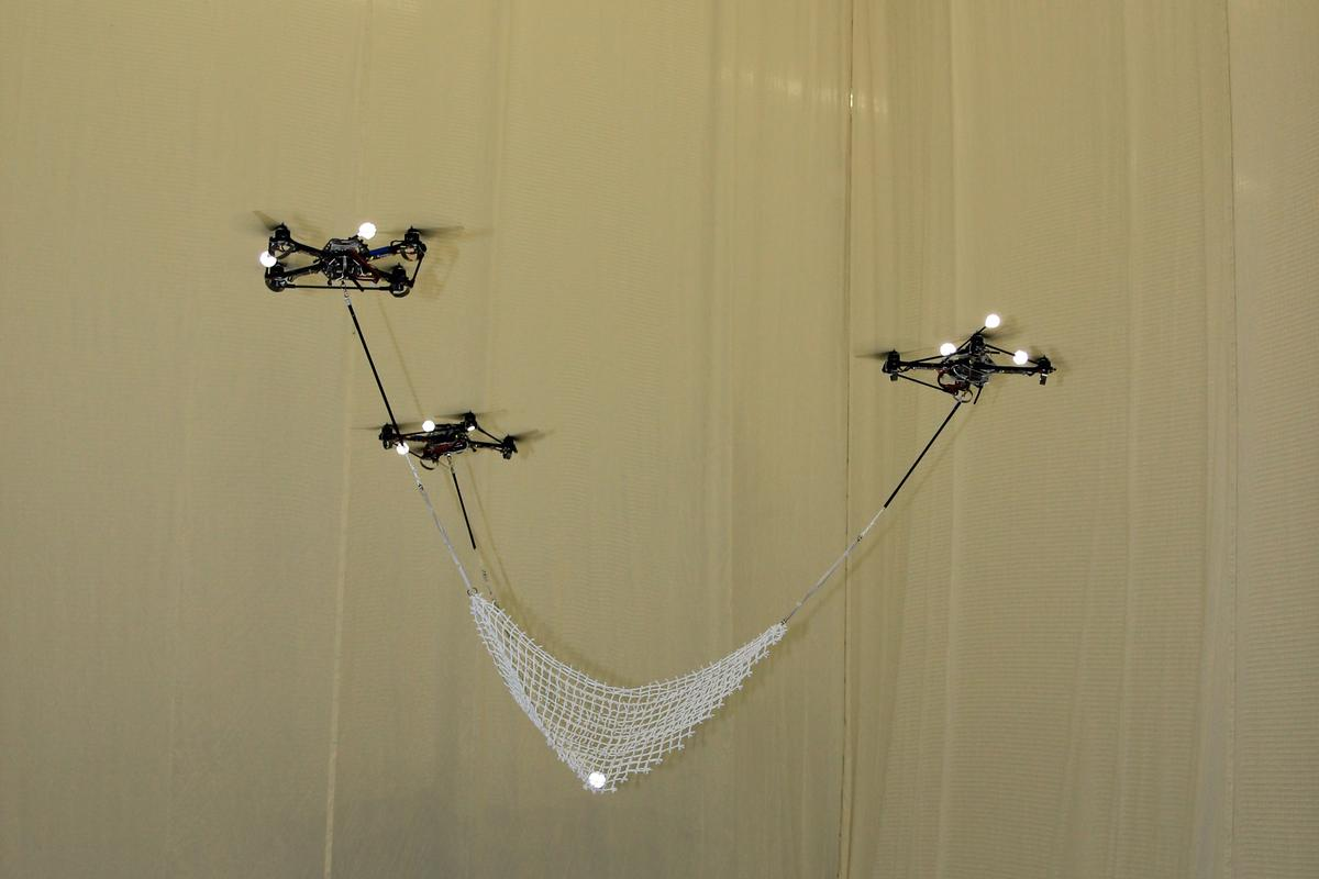 Flying quadrocopters at ETH Zurich's Flying Machine Arena catch and launch a ball using a net spread between them