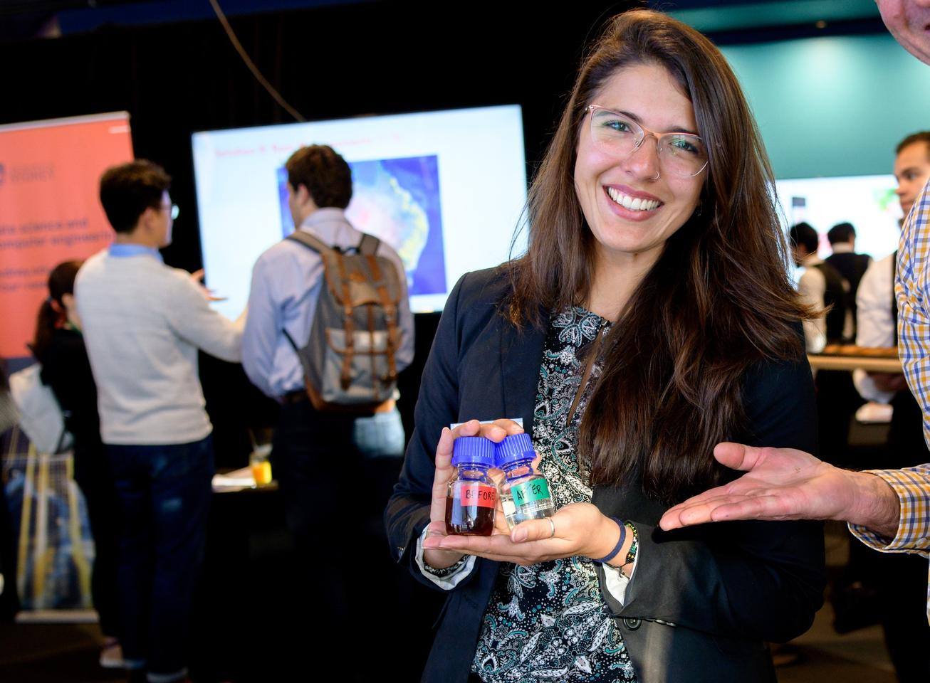 """Lead researcher Julia Ciarlini Jungers Soares holds """"Before and After"""" samples of the wastewater"""