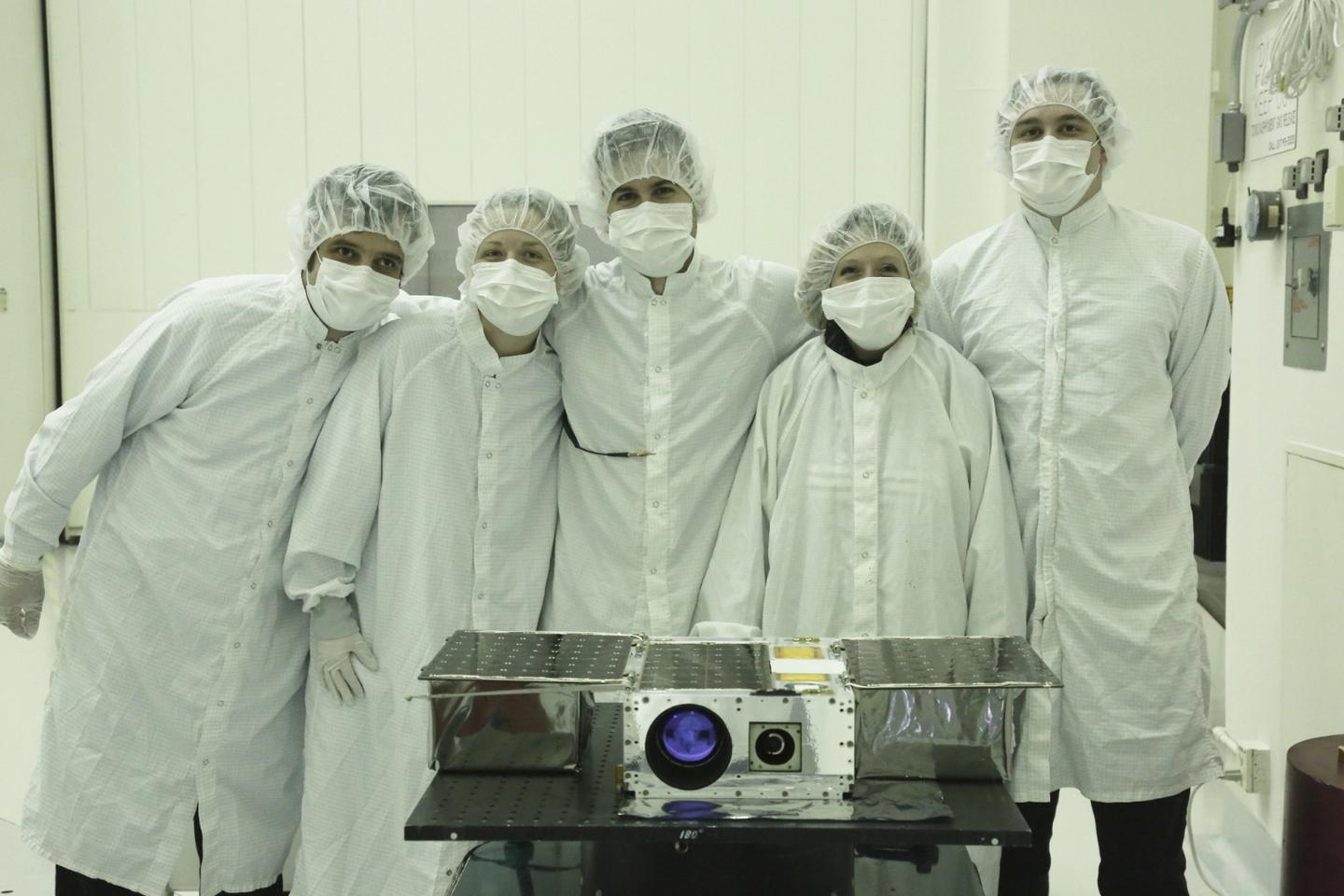 Members of the ASTERIA team prepare the petite satellite for its journey to space