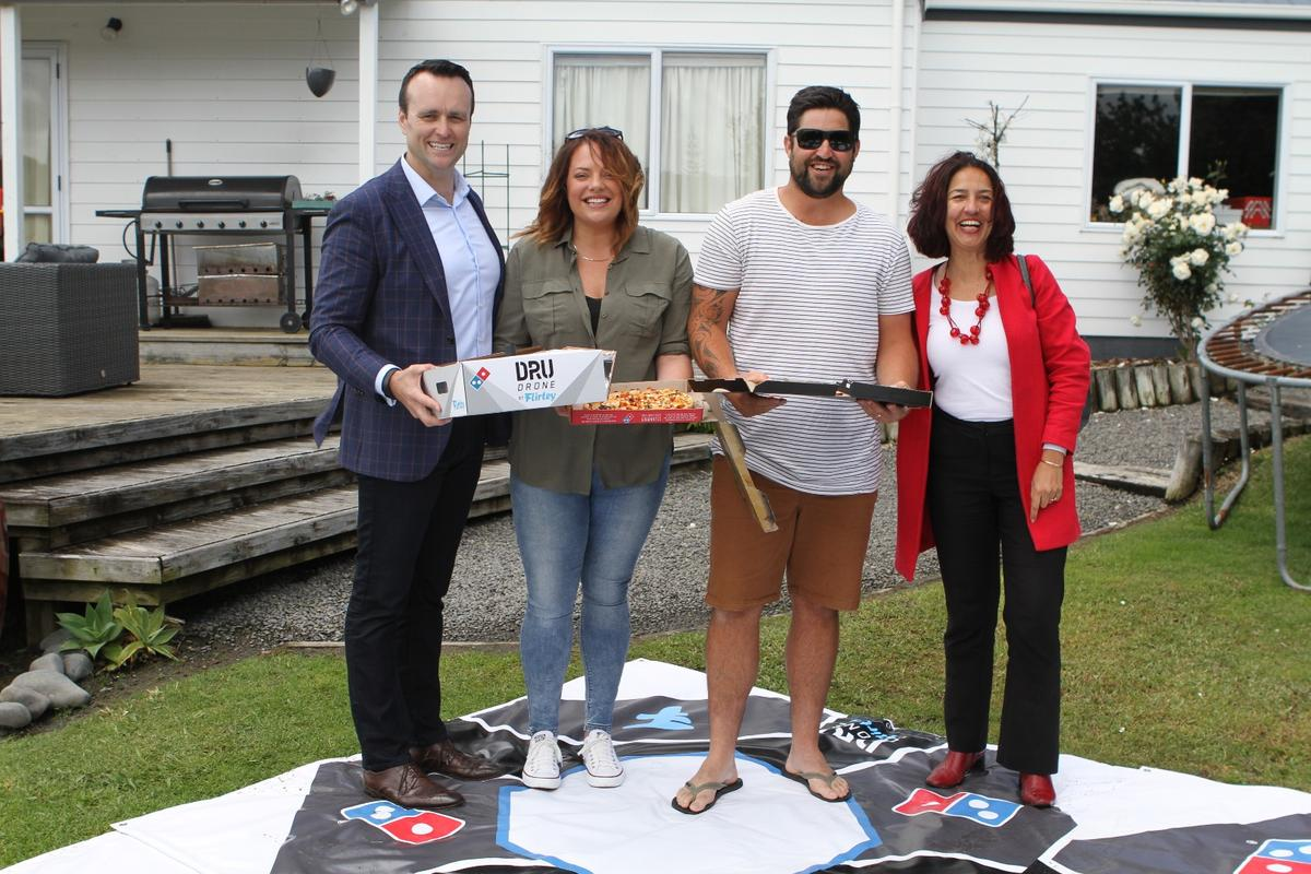Domino's General Manager Scott Bush (left) and Flirtey's New Zealand Director Samantha Sharif (right) with a couple of happy customers in between