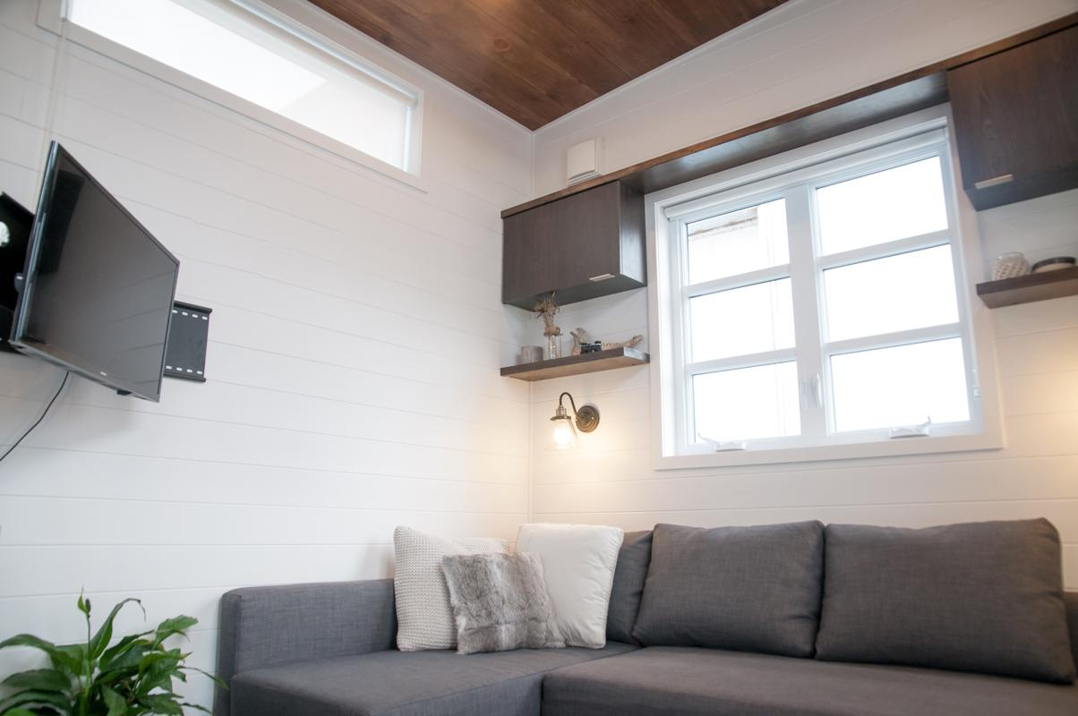 The Laurier's living room includes a sofa bed and wall-mounted TV