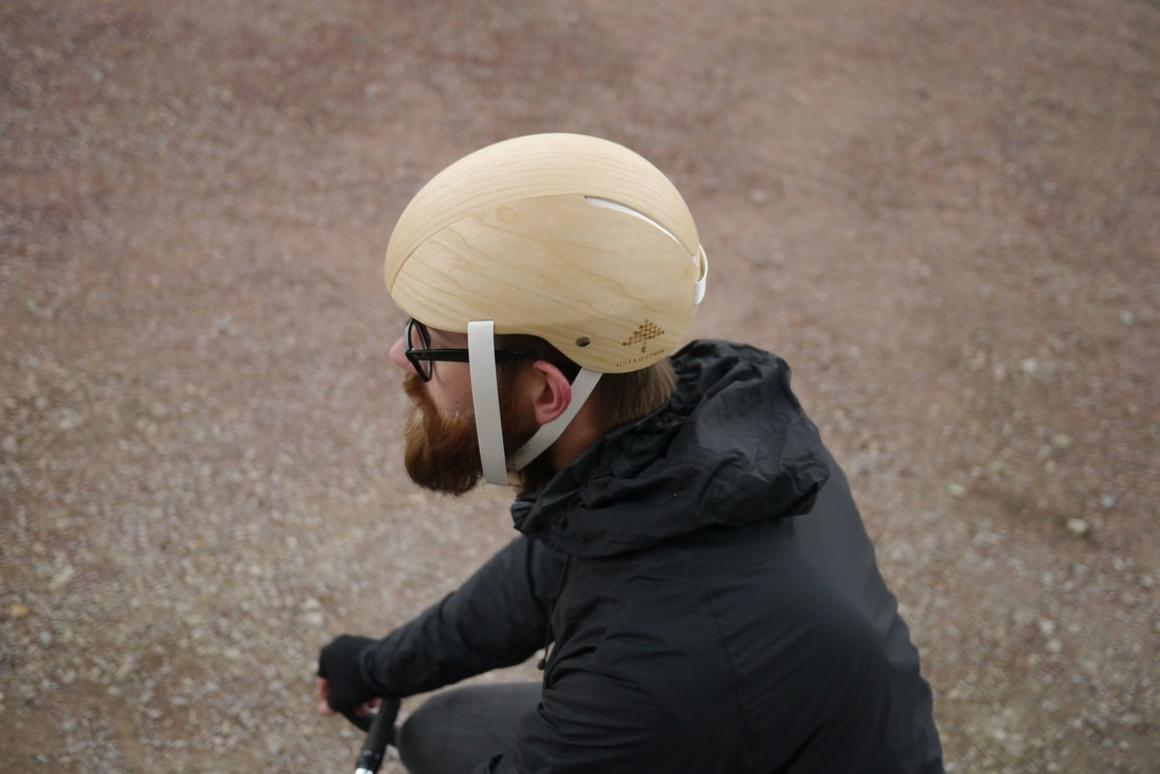 The helmet features a wood outer veneer, wood-based foam on the inside, and paper straps