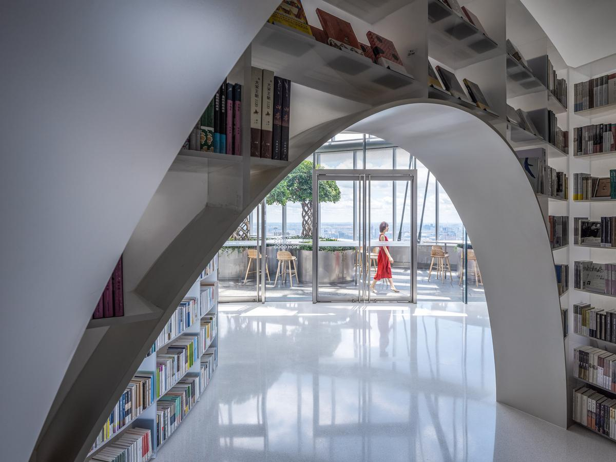 Books over the clouds' interior design is inspired by nature and the white bookshelves are envisioned as mountains