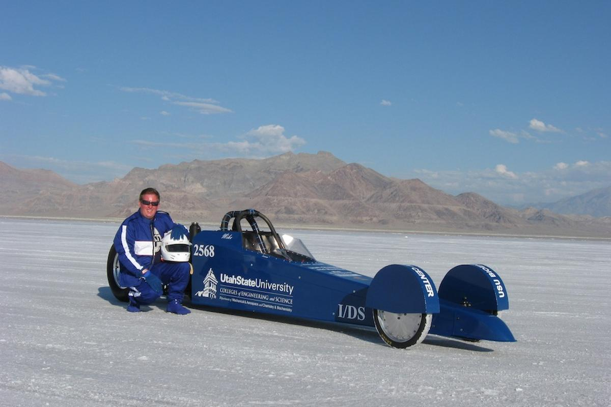 USU biochemist Michael R. Morgan posing beside the Aggie A-Salt Streamliner he piloted at Utah's Salt Flats (Photo: USU)