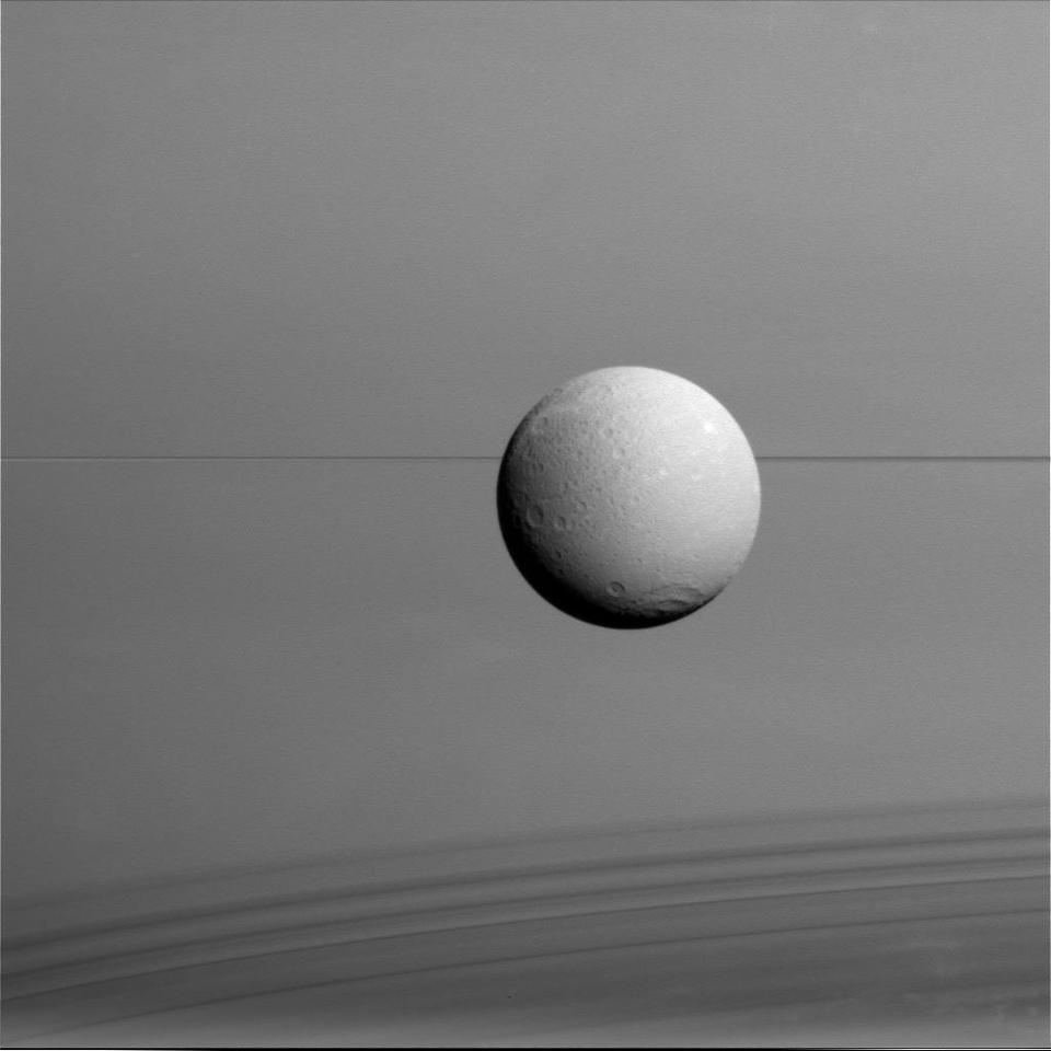 Dione imaged by Cassini at a distance of 45,000 miles (73,000 km) with Saturn in the background