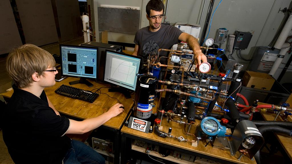 Students, Frederick Welck and Christian Bach, work with an experimental setup for testing valves as part of research led by Purdue University to develop more efficient heat pumps (Image: Purdue University photo/Mark Simons)