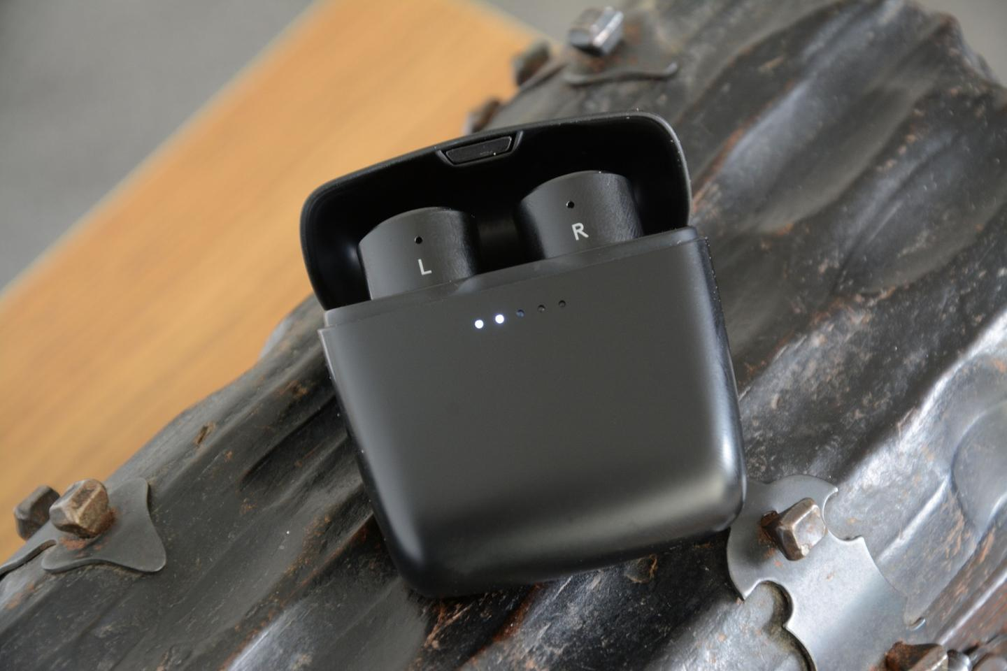 The Melomania 1 earphones are placed in the charging case and the light ring surrounding the multipurpose button begins to pulse, indicating charging is underway