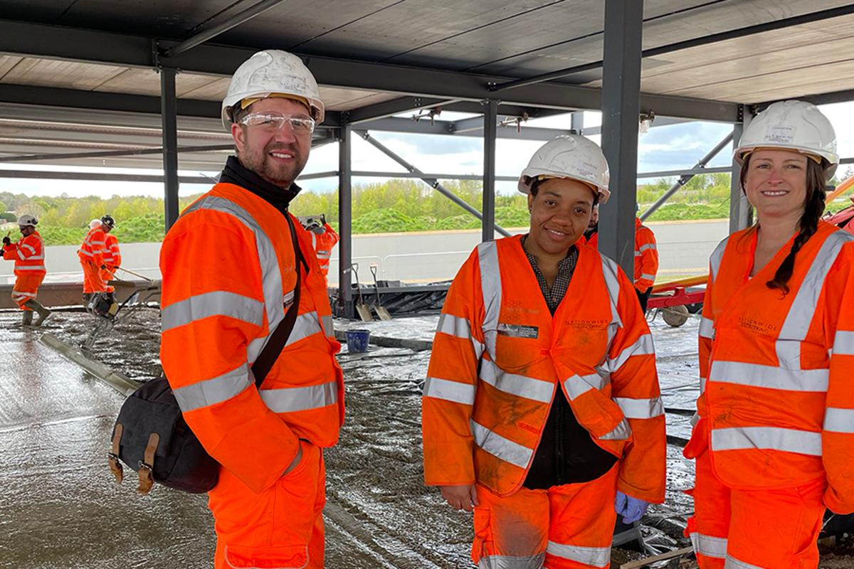 University of Manchester researchers Craig Dawson, Happiness Ijije and Lisa Scullion onsite as workers tend to the world's first graphene-enhanced concrete slab in the background