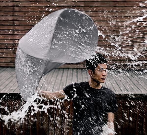 The Rain Shield being tested with a sustained splash of water, with the user remaining dry inside
