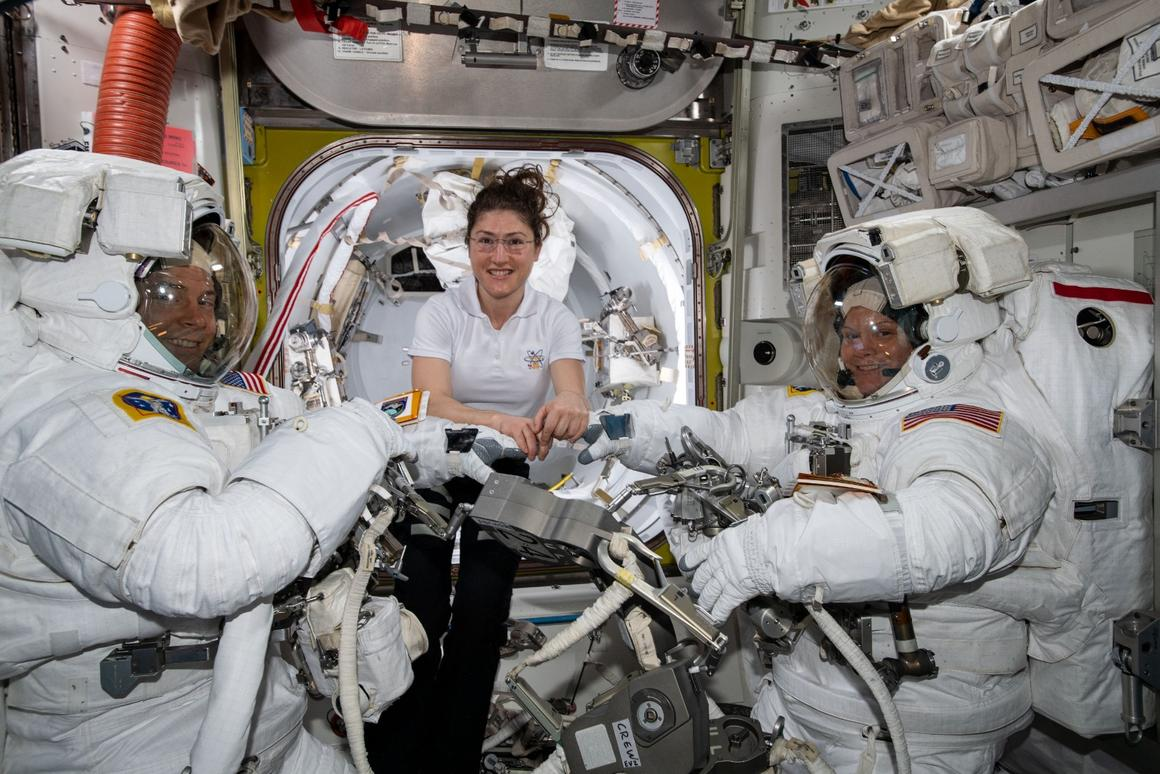 NASA astronaut Christina Koch (center) assists spacewalkers Nick Hague (left) and Anne McClain in their U.S. spacesuits shortly before they begin the first spacewalk of their careers
