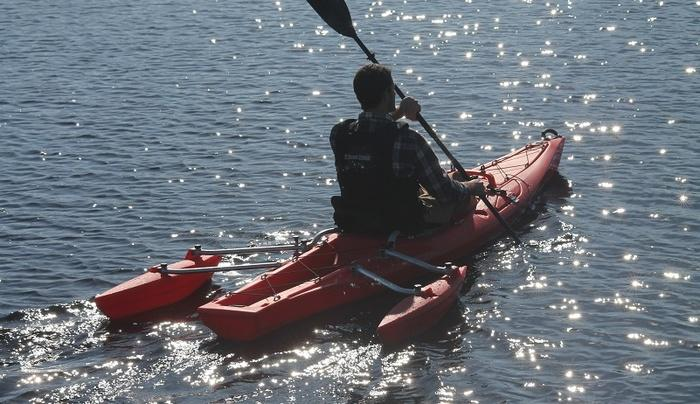 The outriggers are located towards the stern, where they shouldn't interfere with paddling