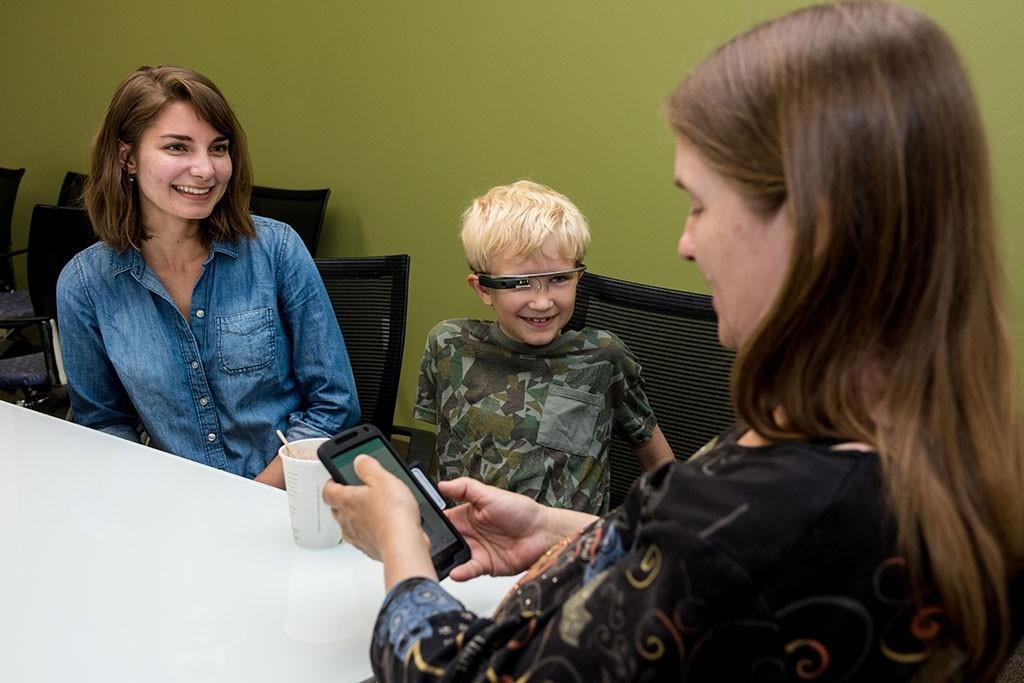 Clinical research coordinatorJessey Schwartz (left) watches as 9 year-oldAlex and his mother,Donji Cullenbine (right), use aGoogle Glass-connectedsmartphone app