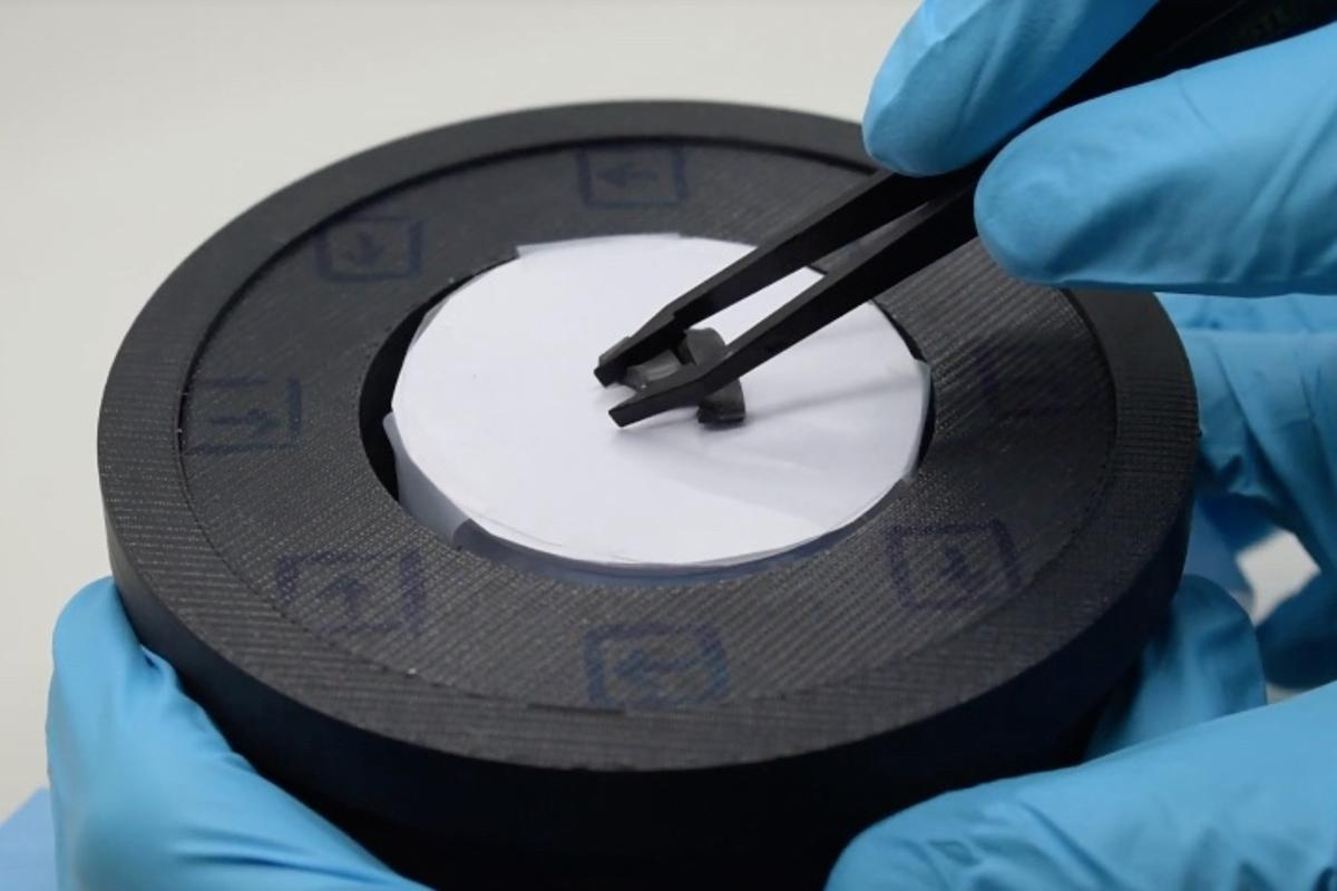 A strip of the material is shaped with tweezers, after which  a ring-shaped magnet will be raised around it