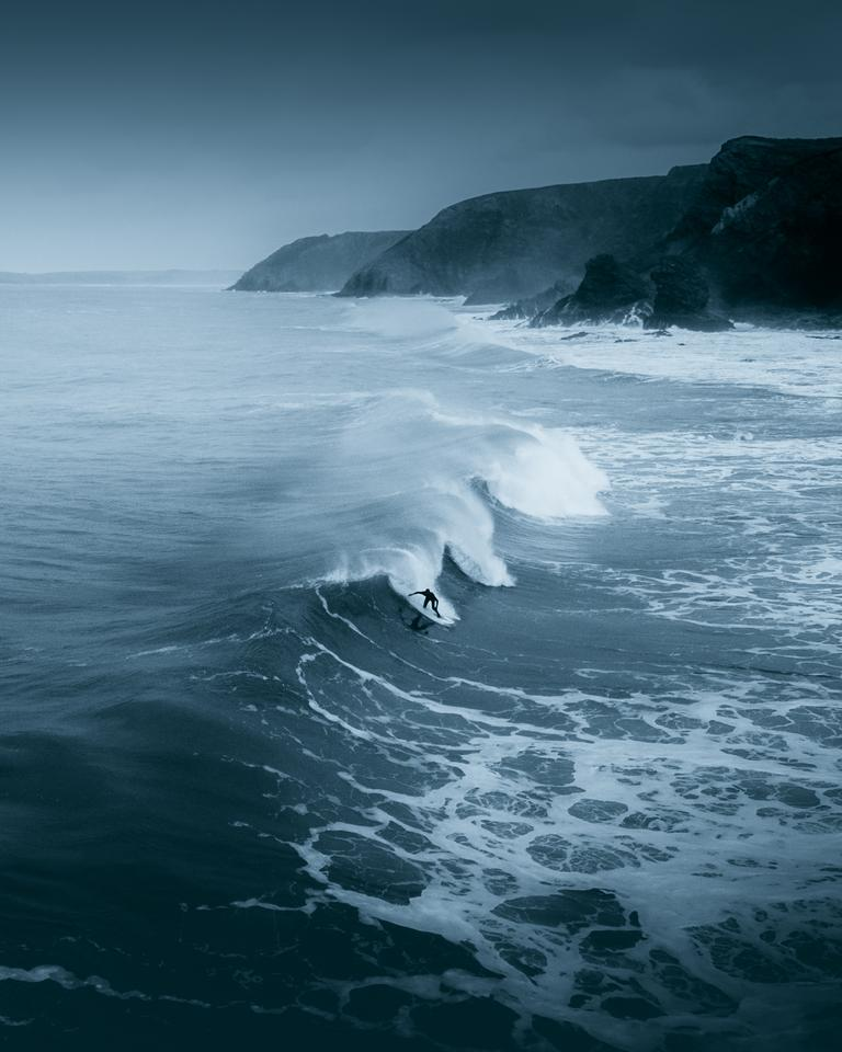 'A lone surfer braving the winter cold on the Cornish North Coast', St. Agnes, Cornwall, UK