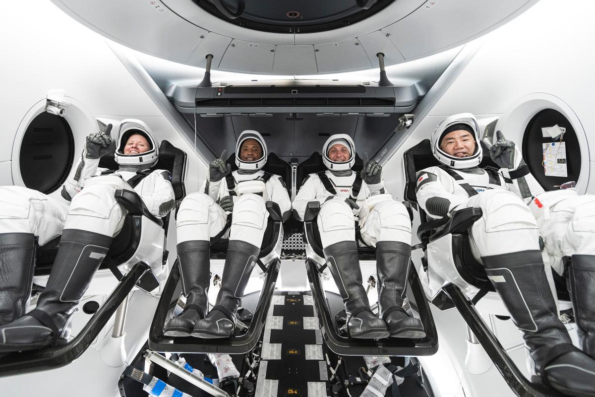 Crew-1 NASA astronauts Shannon Walker, Victor Glover and Mike Hopkins, are seated alongside JAXA's Soichi Noguchi inside the Crew Dragon capsule