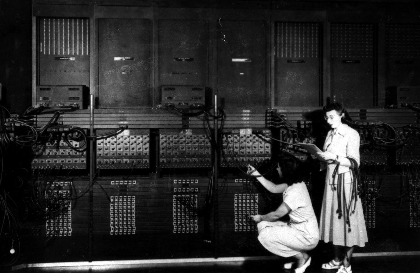 A section of ENIAC with two of its programmers