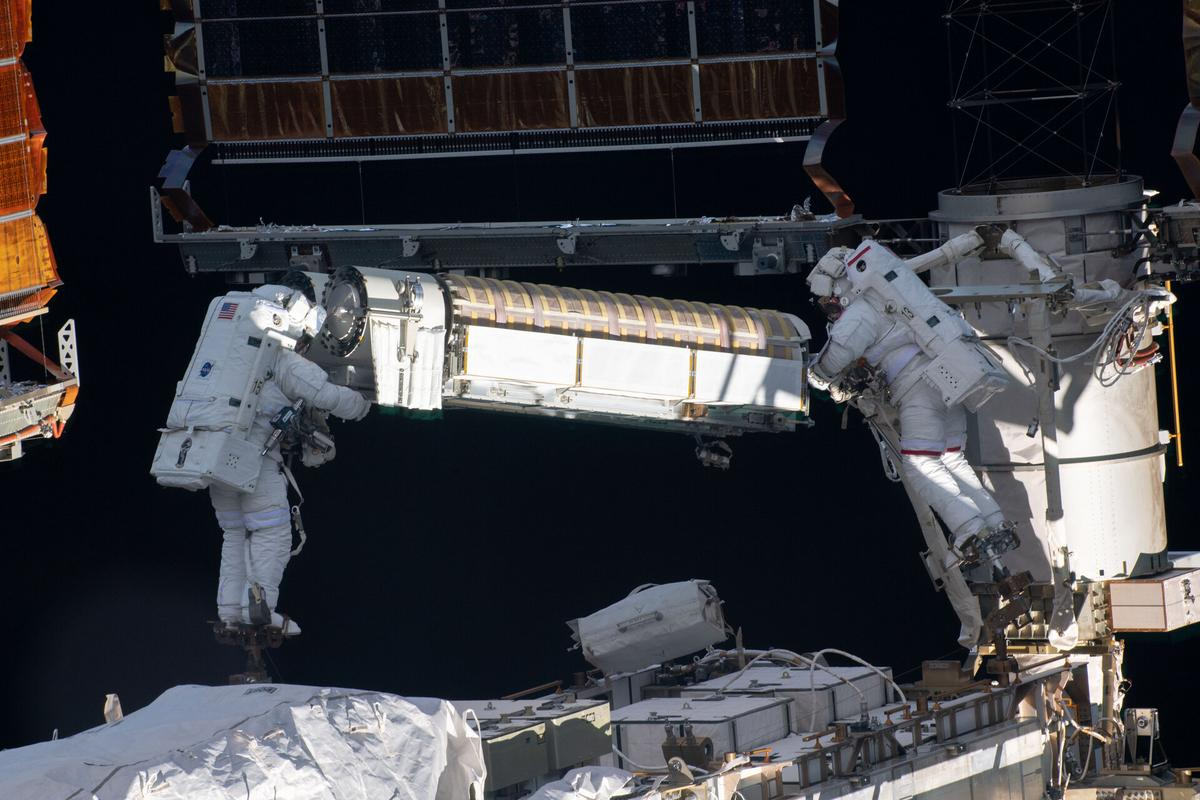 Astronauts Thomas Pesquet and Shane Kimbrough seen transporting one of the new solar arrays to the installation point