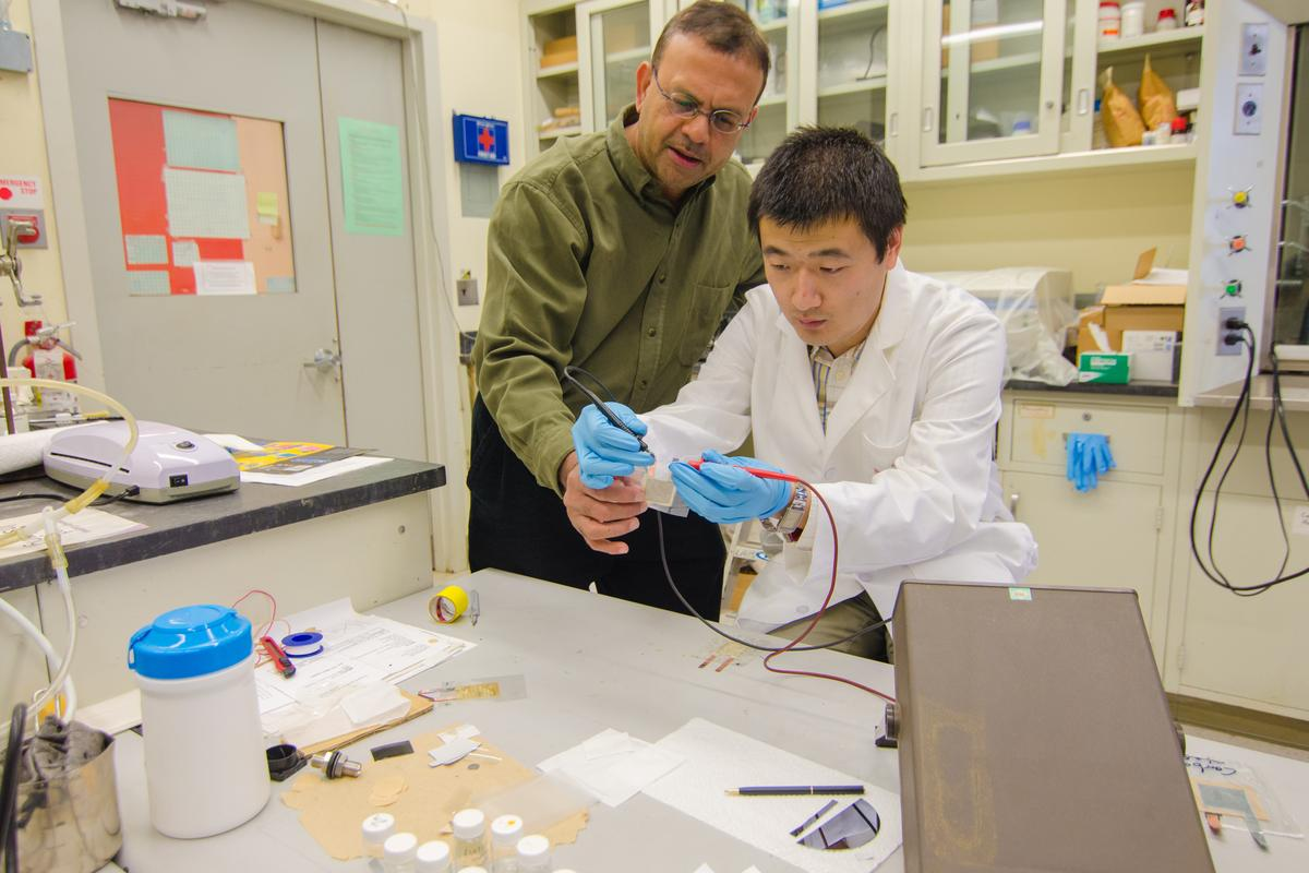 Prof. Som Mitra (left) invented a flexible battery with assistance from Zhiqian Wang, a doctoral student in chemistry (Photo: Jed Medina, NJIT)