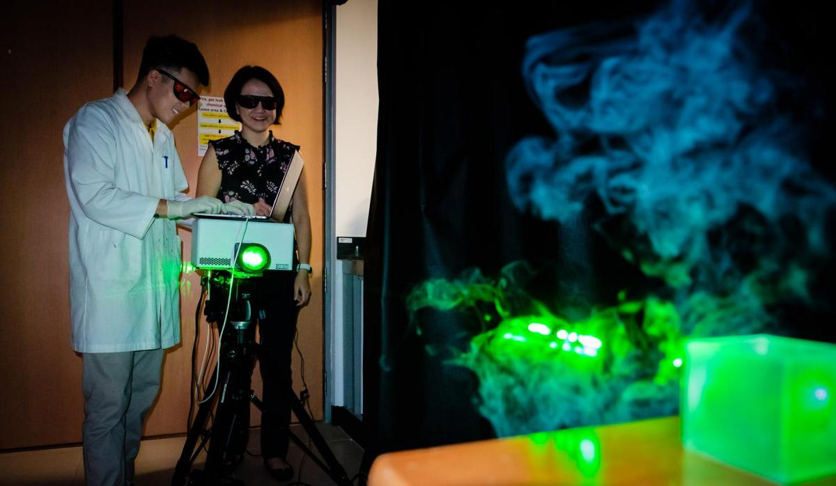 Assoc. Prof. Ling Xing Yi (right) with PhD student Phan Quang Gia Chuong, operating the gas analyzer laser device