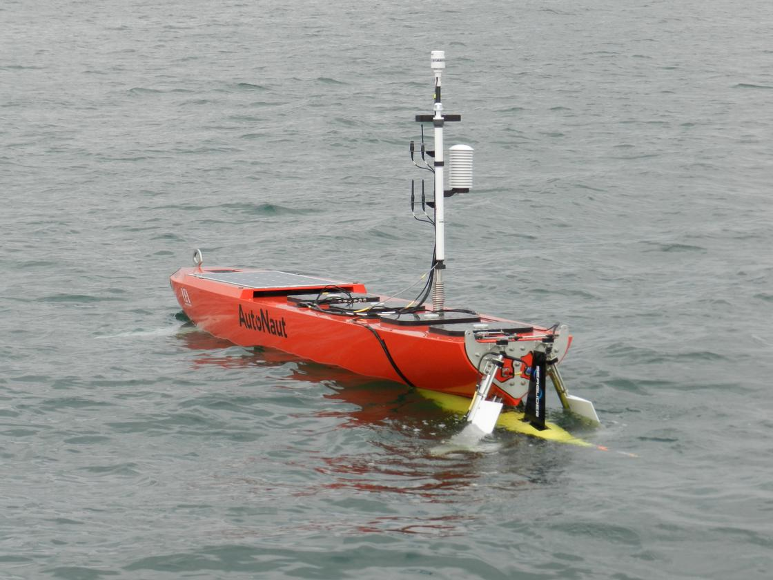 The AutoNaut unmanned surface vehicle measures 5 meters long (16 ft) – the Seaglider AUV (yellow) is slung beneath