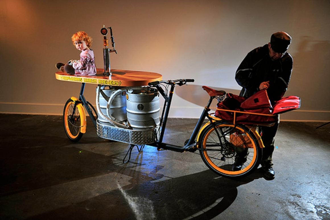 The Beer Bike is a custom-built cargo bicycle that features two beer kegs, a wooden bar with two serving taps, space for pizza boxes, and a solar-powered boom box