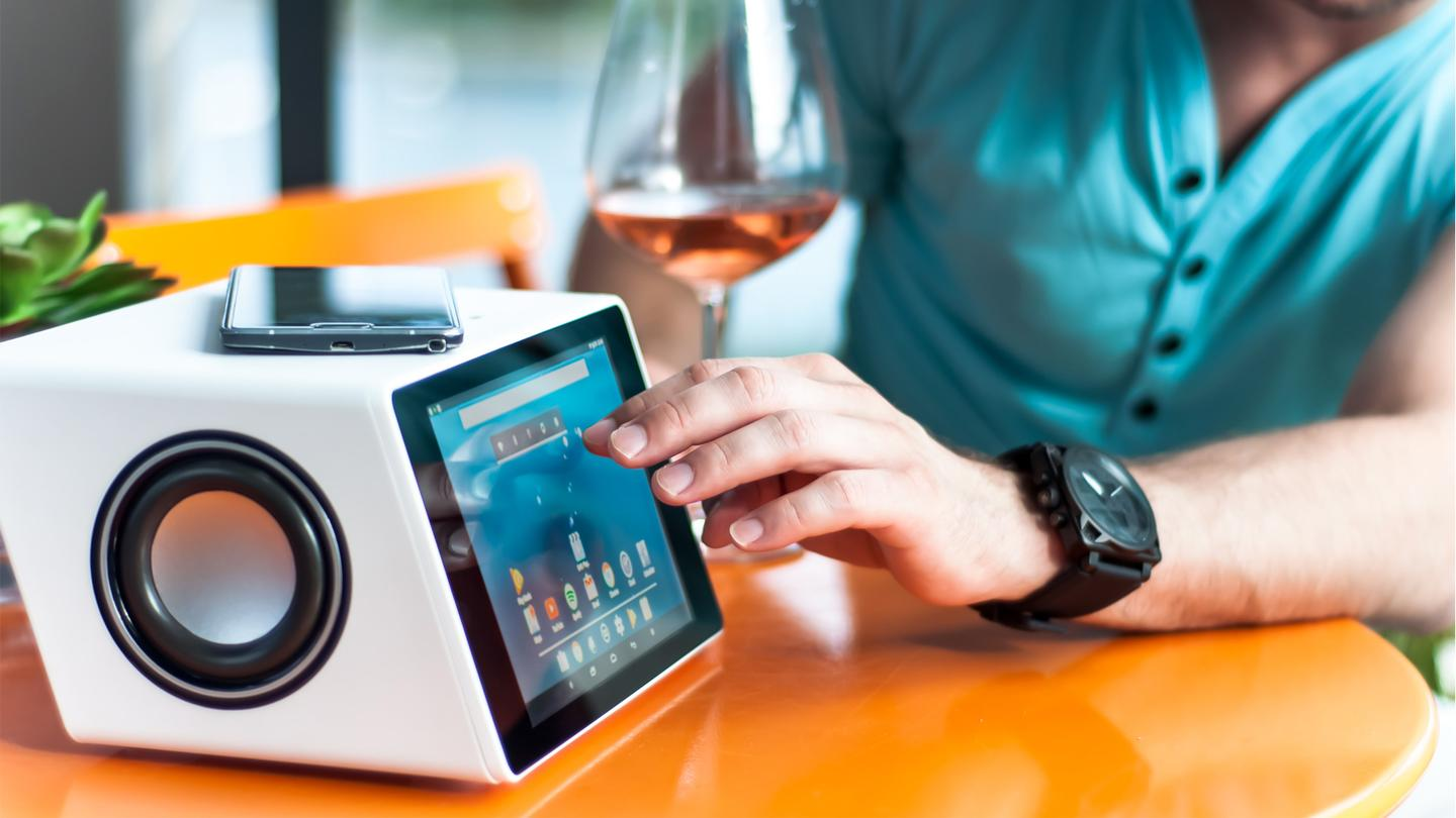 The Aivia smart speaker can be voice-controlled, features a touchscreen display panel, can wirelessly charge devices placed up top and has a B&O-designed subwoofer to the rear