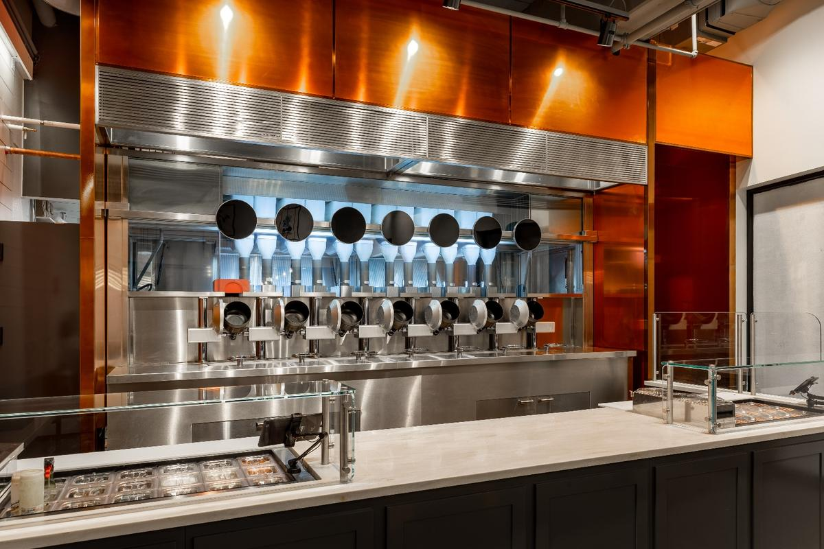 Dishes at Spyce are cooked within view of customers, in seven induction-heated rotating woks