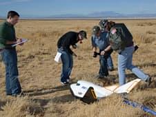 Left to right: Sierra Nevada Corp.'s Zachary Krevor, Univ. of Colorado's Eric Hall and Ryan Starkey, and Sierra's Merri Sanchez, perform a post-landing inspection of Sierra Nevada's Dream Chaser scale model following its successful drop flight. (Photo: NASA / Tony Landis)
