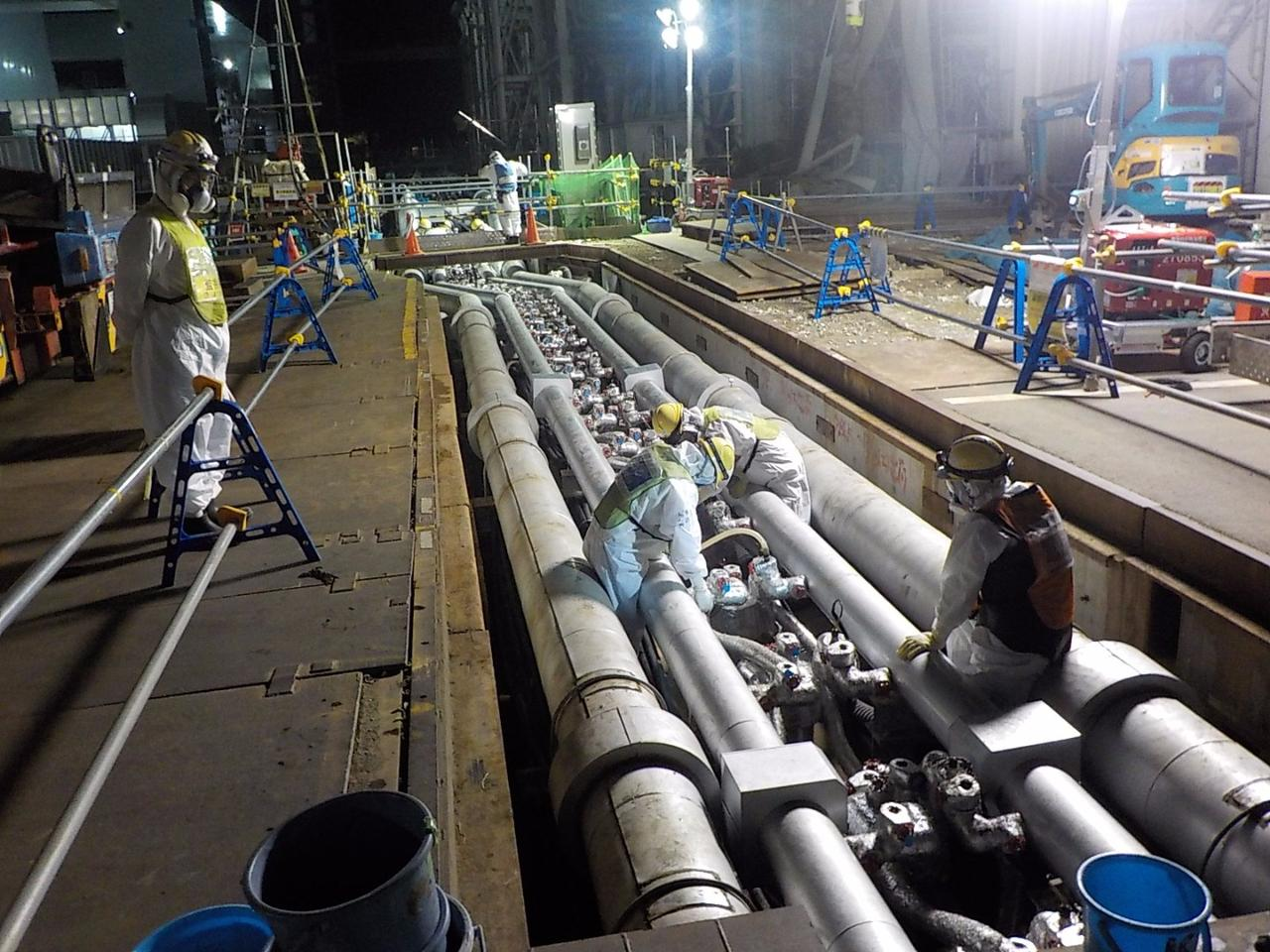 Fukushima workers pour brine into the refrigerated pipes