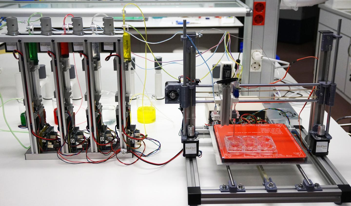 The skin-making bioprinter, with the bio-inks at left at the print bed at right