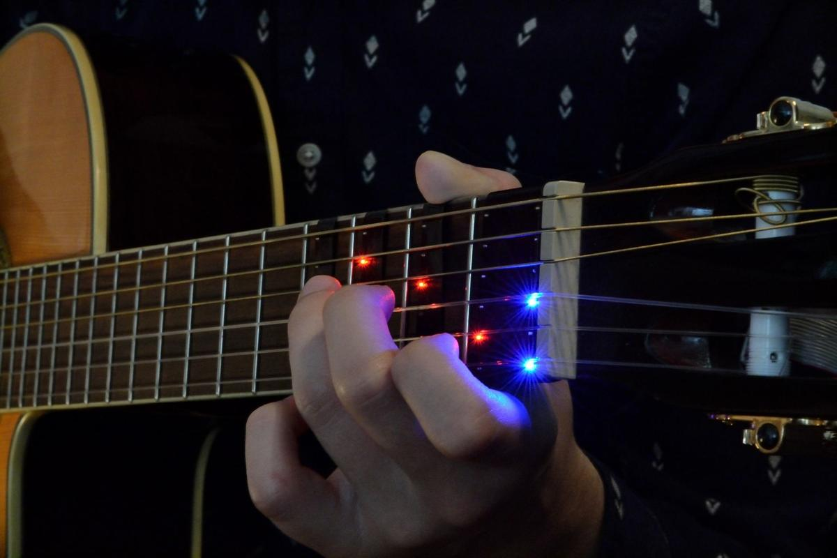 The FretX sleeve wraps around the guitar neck and connects over Bluetooth with a smart device running a companion app