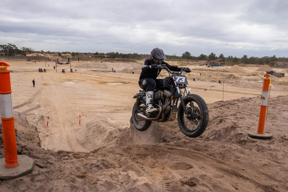 That's how we do it! Flat track styled Harley takes a leap at the end of a successful hill climb