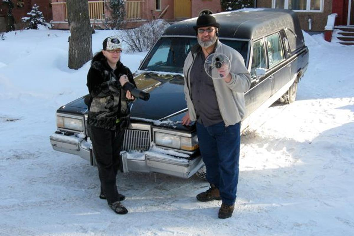 Paranormal investigators Rona Anderson and Ben Myckan sporting some of their ghost-hunting gear in front of their hearse, Nocturna