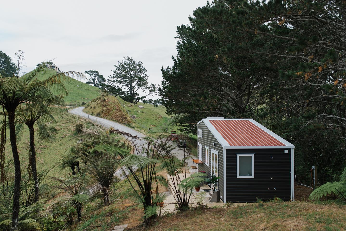 The Cherry Picker Tiny House is located in a picturesque spot overlooking the ocean in New Zealand