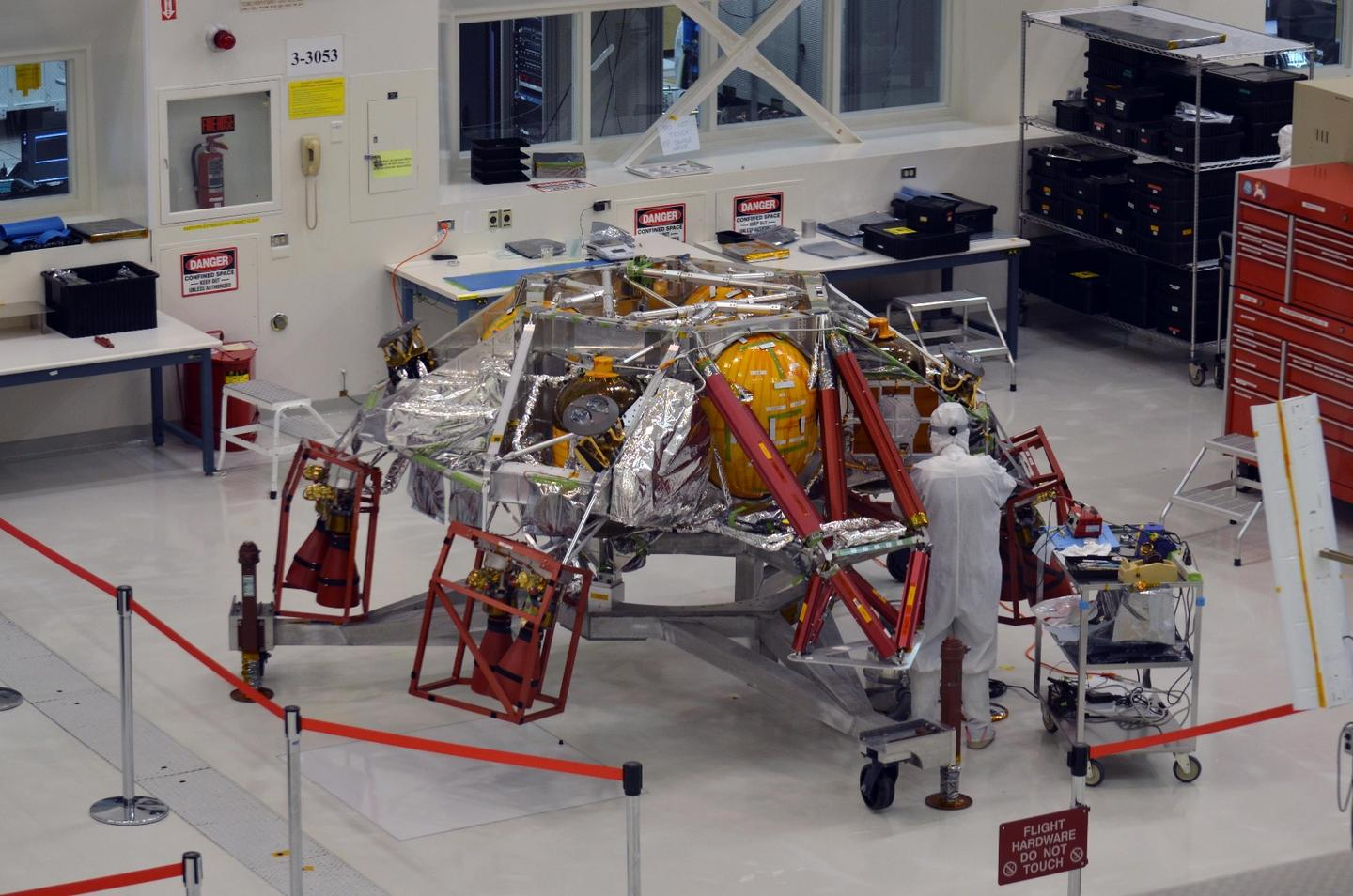 A technician works on the descent stage for NASA's Mars 2020 mission inside JPL's Spacecraft Assembly Facility