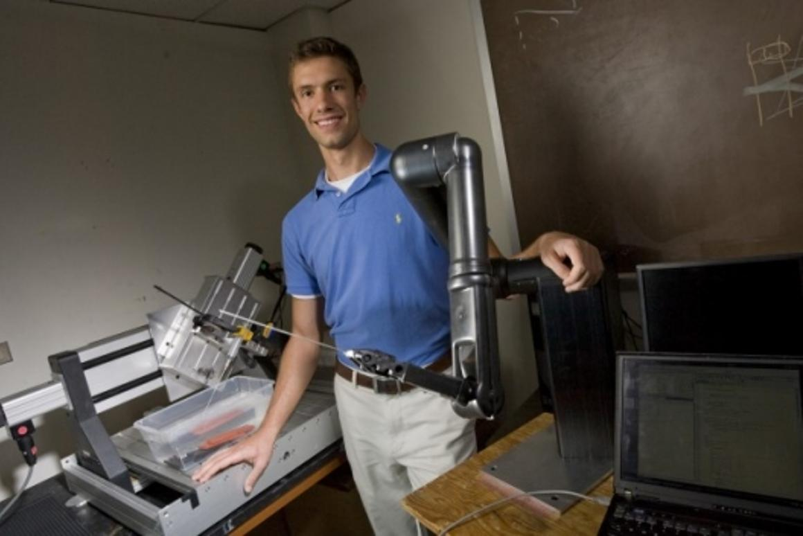 Research team member A. J. Rogers with the shrapnel-finding surgical robot