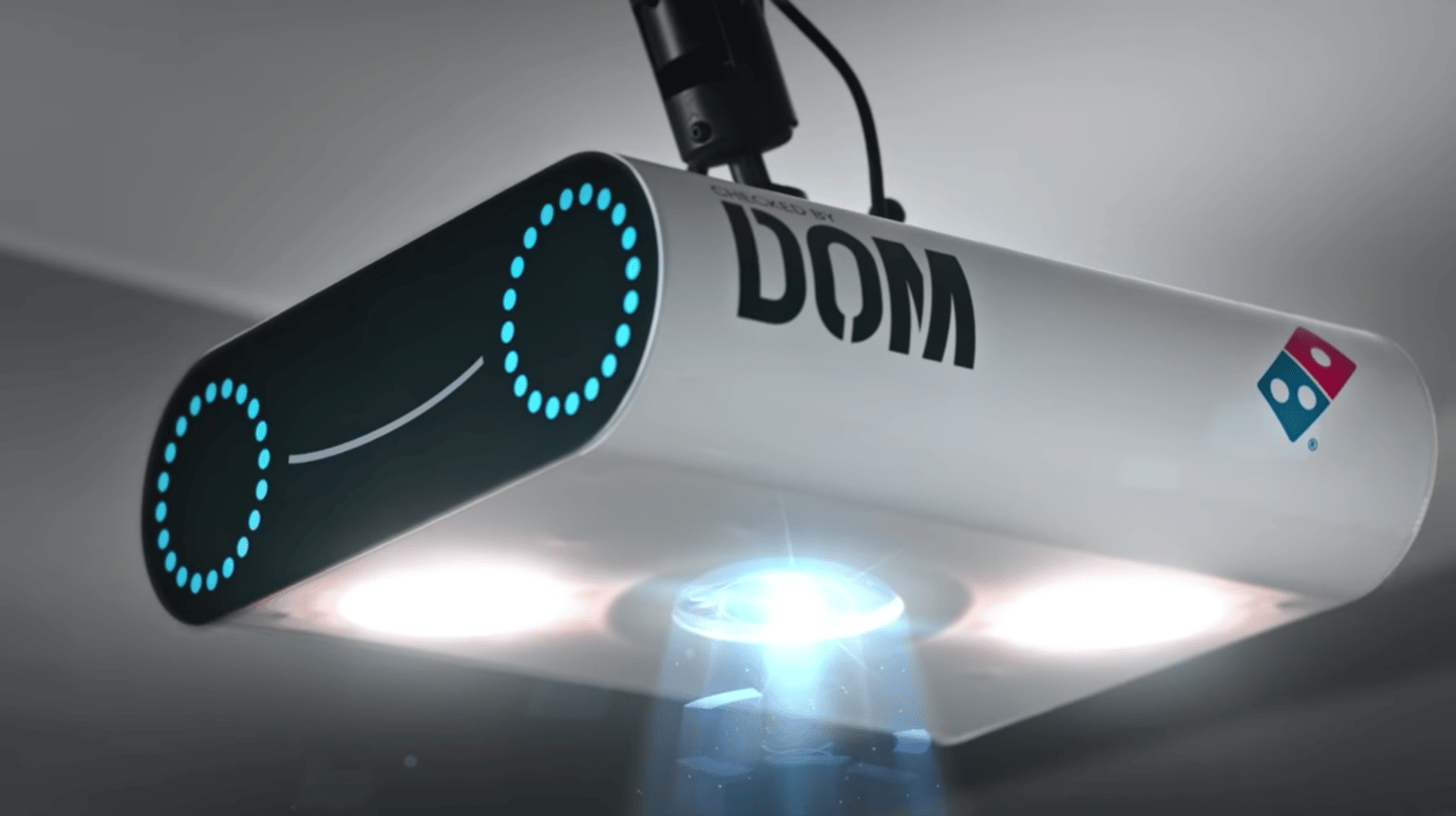 The technology is built into a scanning device called the DOM Pizza Checker, which sits above the cut bench to run a final inspection on Domino's pizza pies before they're handed over to the delivery person