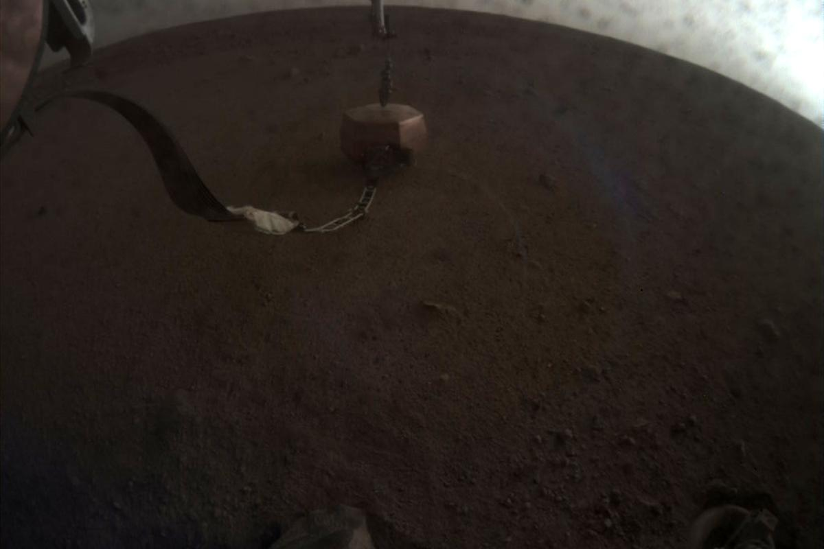 The InSight Mars lander has just used its robotic arm to gently deposit its main instrument, a sophisticated seismometer (copper-colored in the picture), on the surface of the planet