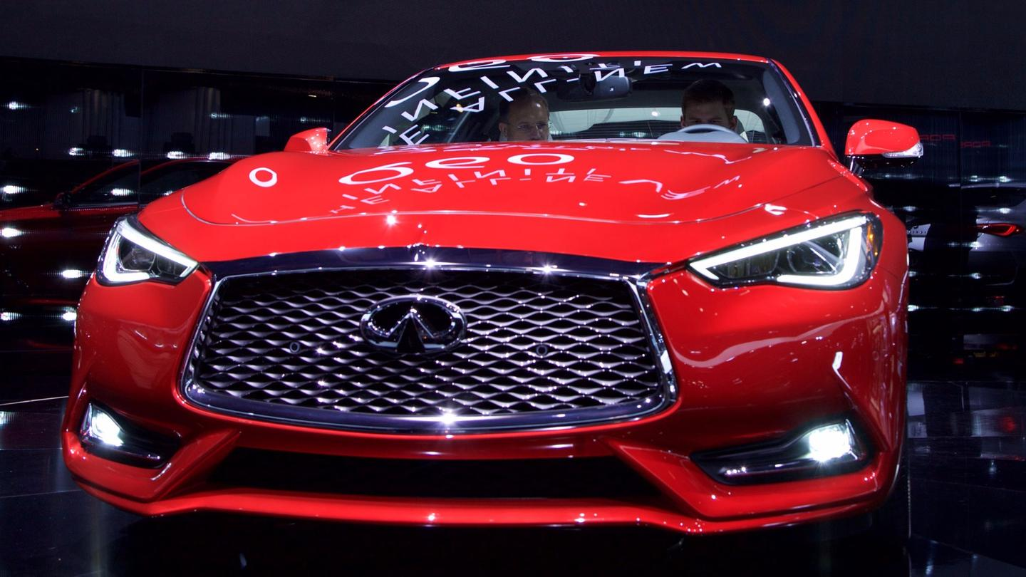 The new Q60's front fascia is dominated by a wide grille flanked by thin, peering headlamps, below which a trapezoidal intake opens