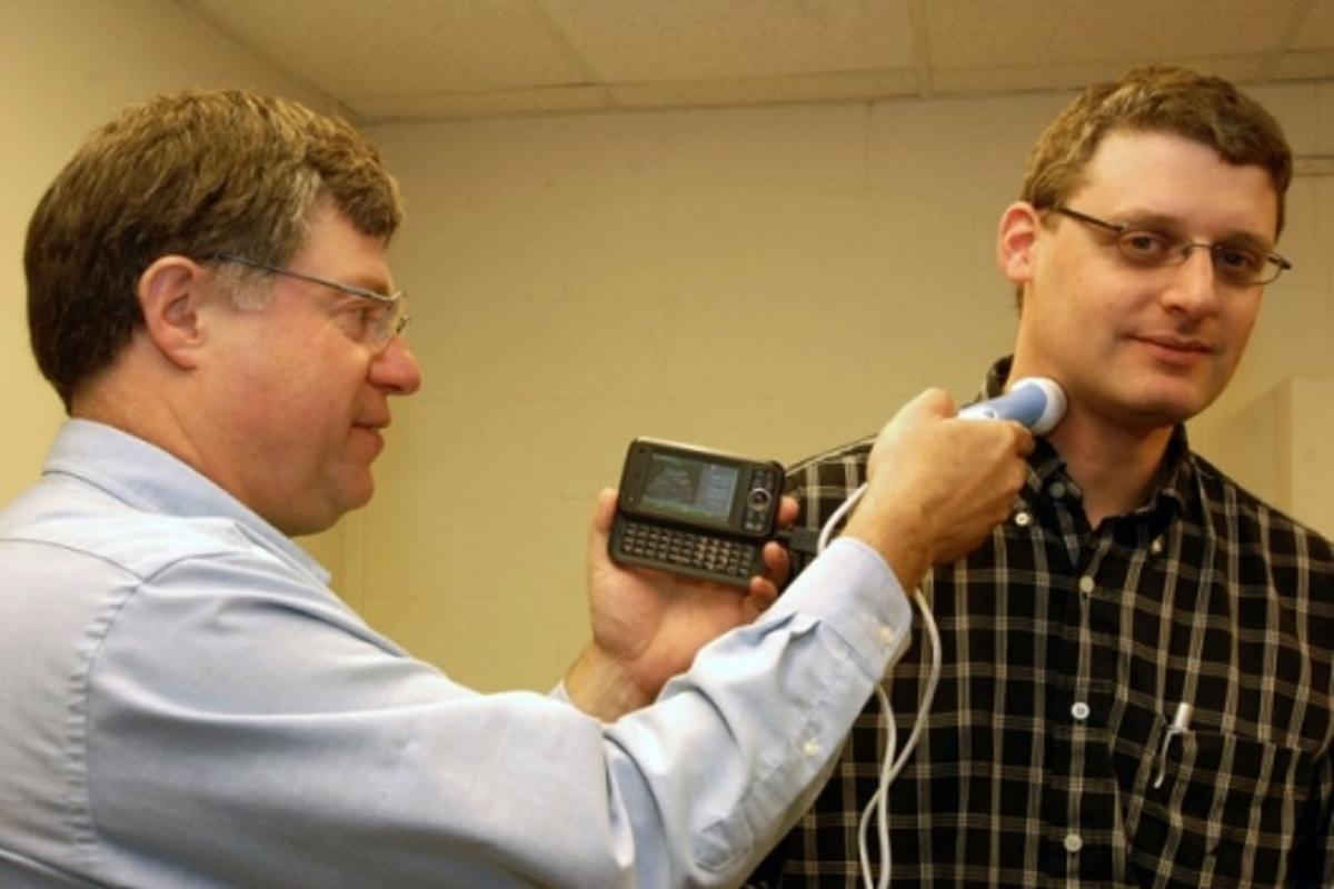 Dr William Richard (left) takes an ultrasound probe of colleague David Zar's carotid artery with smartphone-compatible USB ultrasound probe he designedPhoto credit: David Kilper/WUSTL Photo