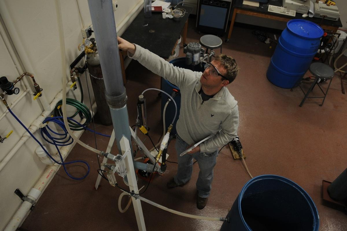 The CO2 collecting smokestack with Michigan Tech chemical engineering PhD student Brett Spigarelli (Photo: George Olszewski)