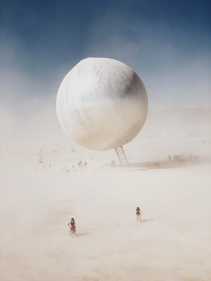"""3rd Place,Photographer of the Year. Come Across, Nevada, iPhone X. """"I took this photo in the desert in Nevada, USA, at the Burning Man festival. I stood on a bridge and saw two people lost in a sand storm, but after a while, something very special came along,a huge silver ball."""""""