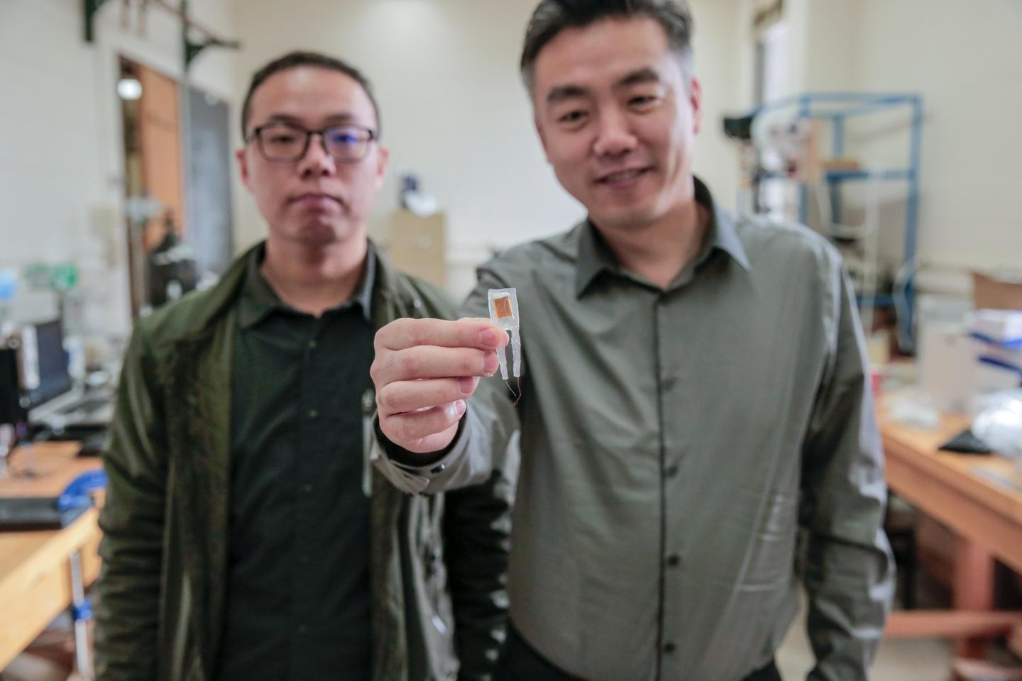 Graduate student Guang Yao (left) and Xudong Wang (right) hold a small implantable device that helped rats lose 40 percent of their body weight