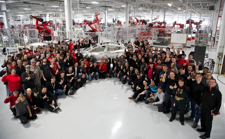 Tesla employees celebrate construction of the first customer Model S body
