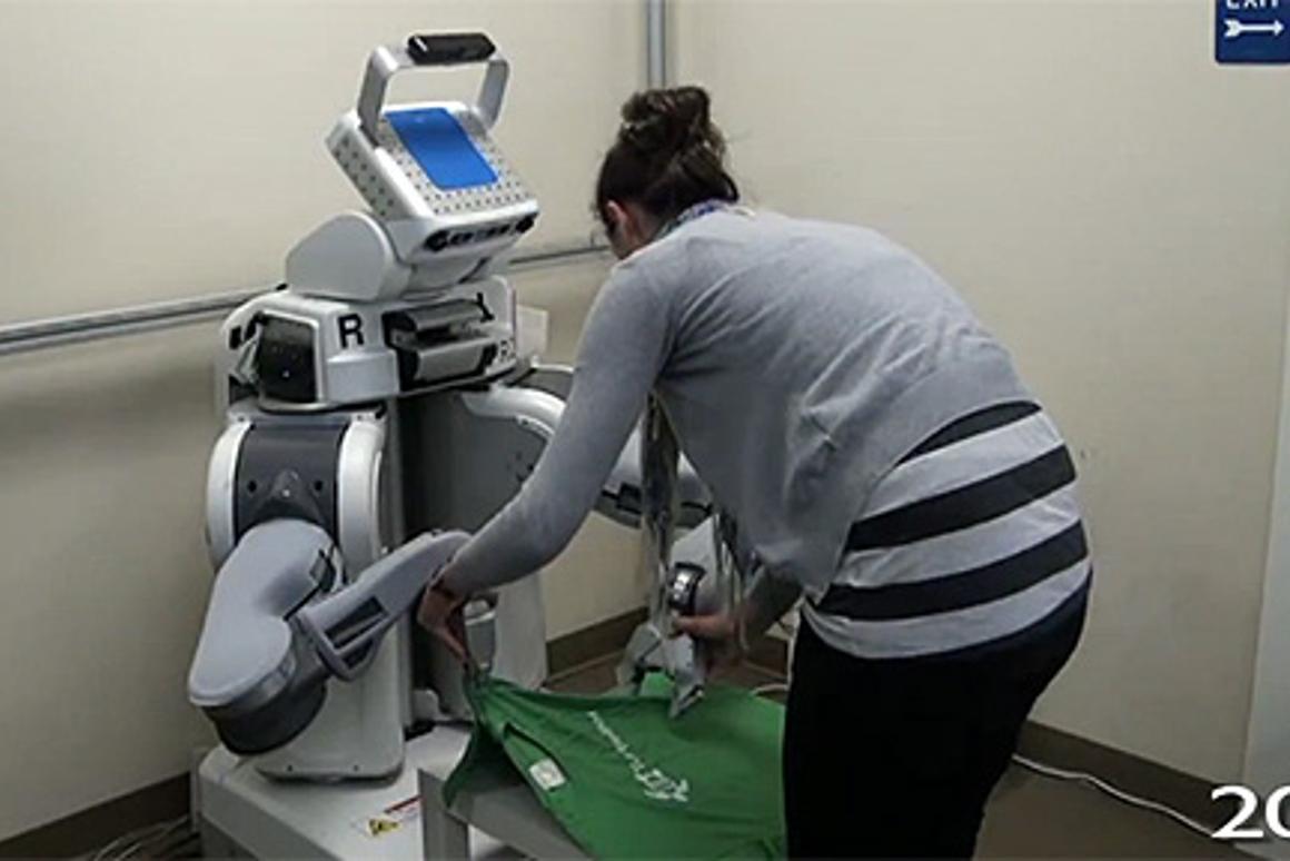 A test subject teaches the PR2 robot how to fold a t-shirt through demonstration