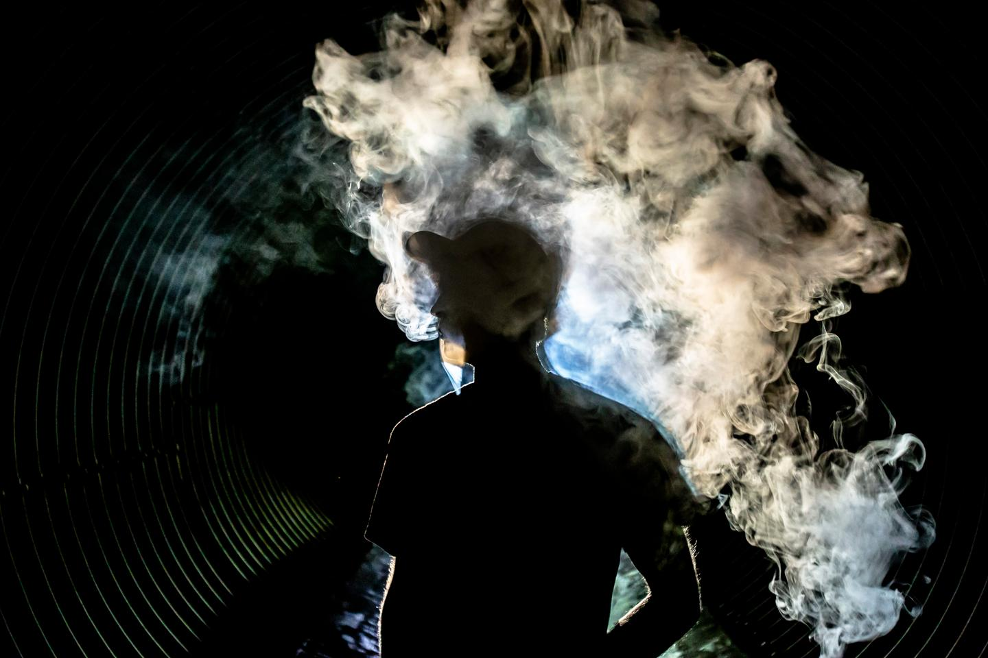Man with smoke lifting from body in a dark tunnel
